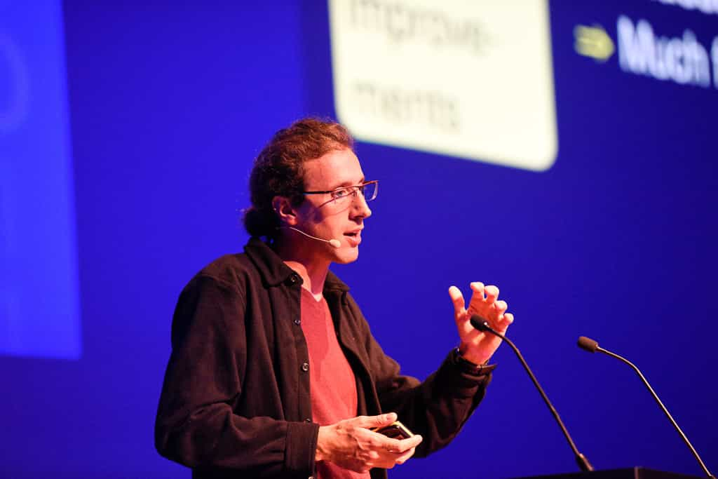 Gaël Varoquaux speaking onstage in front of microphones at the Amsterdam Spark Summit 2019.