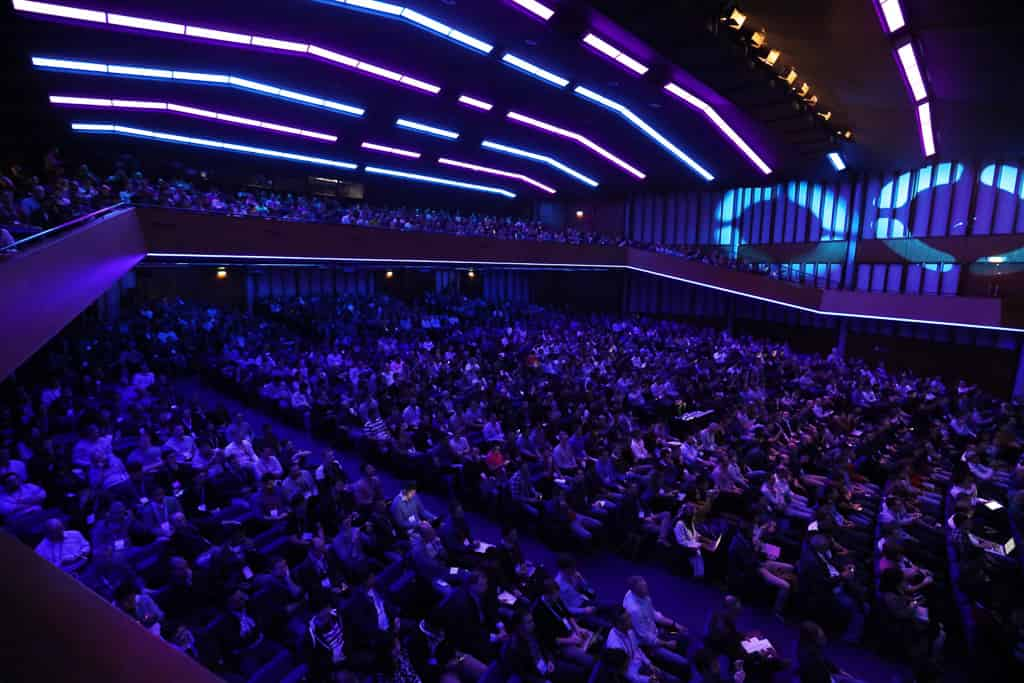 A view of the convention center theater from the balcony above, with attendees from Spark + AI Summit Europe in nearly every seat.